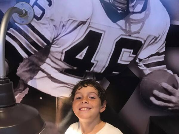 Smiling boy in front of football player mural